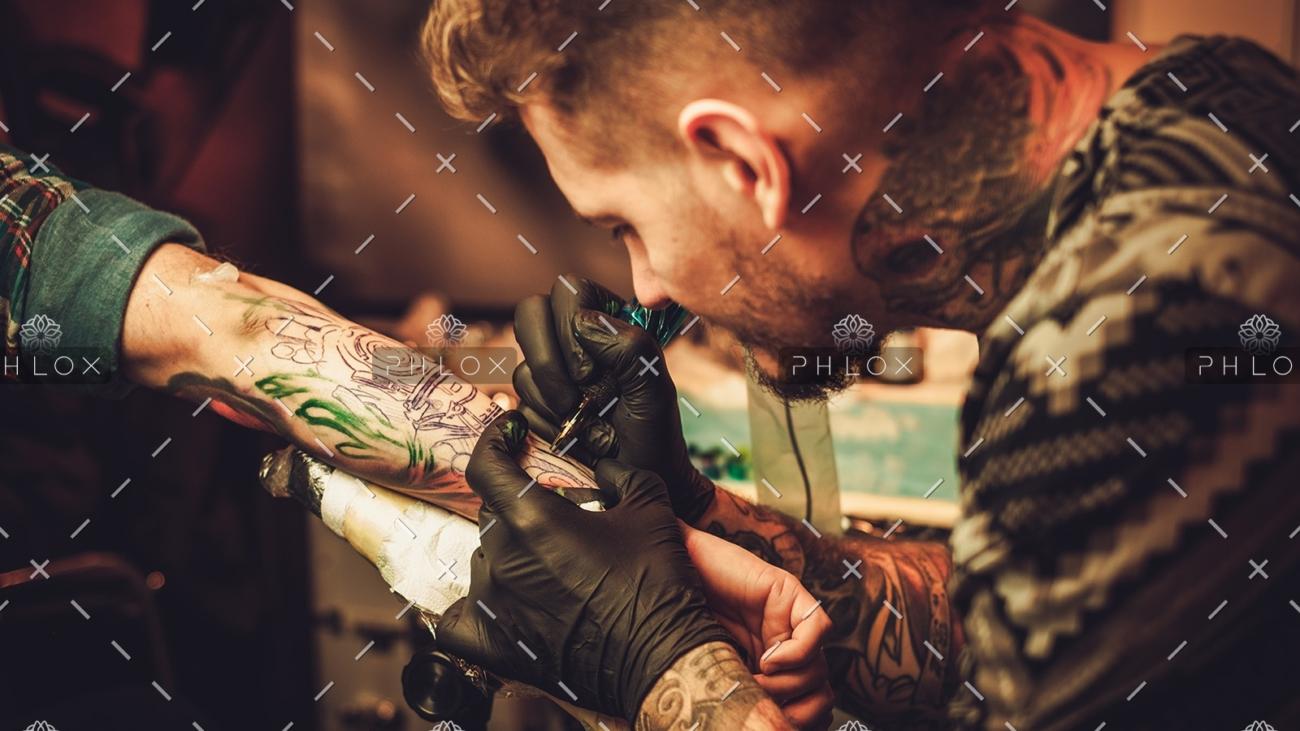 demo-attachment-354-tattoo-artist-makes-a-tattoo-on-a-mans-hand-PECZRE2-1